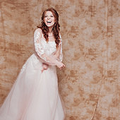 Happy laughing young woman in wedding dress with long sleeves. Young redheaded woman in wedding dress