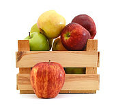 Apples and pears in wooden crate isolated on white background