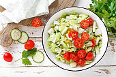 Healthy vegetable salad of chinese cabbage, corn, cucumbers and tomatoes. Delicious vegetarian dietary lunch. Vegan food. Top view. Flat lay