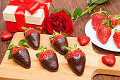 Fresh strawberries dipped in dark chocolate, gift and heart on wooden background. Valentine's Day.