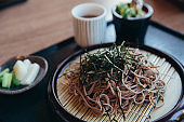 Soba noodles with soup on wood background