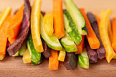colorful carrots and cucumbers vegetables julienned for salad on wooden cutting board, concept raw food, close up