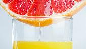 Macro image of juice flowing from fresh grapefruit in glass