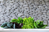 Leaves of green and red lettuce, kale, amaranth on white table with stone background.