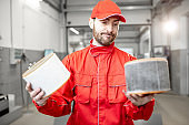 Auto mechanic with new and used car air filter