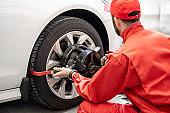 Auto mechanics making wheel alignment at the car service
