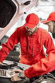 Auto mechanics doing diagnostics with laptop