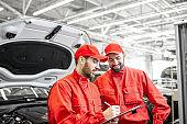 Auto mechanics examining car indoors