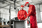 Auto mechanics with wrenches at the car service