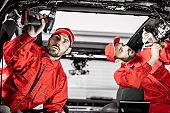 Car service workers disassembling car interior
