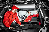 Car service workers disassembling car interior