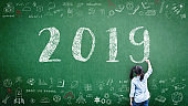 2019 class new calendar year greeting by kid's hand drawing on school teacher's chalkboard with student's educational doodle for new academic year, education semester, classroom schedule concept