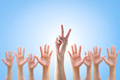 Leader's two fingers victory sign among blur hands crowd group for World participation, leadership, volunteer concept