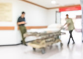 Blur background male nurse staff working on hospital corridor hall pushing patient stretcher bed in-out emergency room