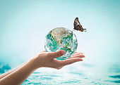 World ocean day,, saving water campaign, sustainable ecological ecosystems concept with green earth on woman's hands on blue sea background : Element of this image furnished by NASA