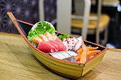 Set of sashimi in wooden ship bowl consist of Toro, salmon (sake), octopus (tako), tuna (maguro) and imitation crab stick put on ice - Japanese food concept.