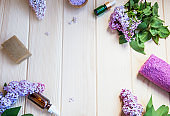 Organic skincare and spa products with lilac flowers, bath salt and oil bottles , natural soap , home-spa setting still life, organic products for body and skin