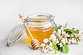 Raw organic acacia flowers honey jar with dipper and acacia flowers