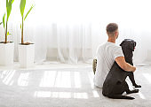 Home concept of relaxation and comfort. A guy with a dog at home in a beautiful interior.