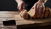 man cutting fresh bread on wooden table