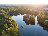Beautiful countryside landscape picturesque river with ships, green forest with summer sky at sunset. Aerial view from drone at Sofiyivsky park, city Uman, Ukraine