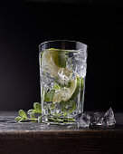 Delicious refreshing lemonade with ice and mint on dark