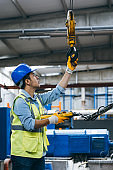 Young businessman holding and working with remote control for operating crane
