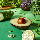Fresh organic green vegetables - half of avocado, lime, cucumber, greenery on a duotone paper background.