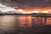 landscape, Floating house whit old wooden boat and sunset at Vajiralongkorn Dam in Kanchanaburi, Thailand.