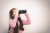 Little girl explorer is looking through binoculars'n