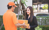 Delivery man in orange bringing woman the package