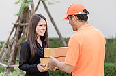 Woman receiving a delivery box from delivery man