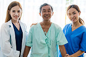 attractive asian woman nurse and doctor working with smiling and freshness together to takecare ill old senior patient in hospital