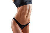 Beautiful super fit young woman showing off her perfect muscular ripped abs. Fitness model. Perfect Slim Body. Studio shot. Fitness trainer with ideal abdominal belly
