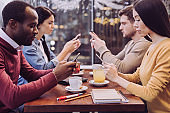 Thoughtful four friends texting in social media
