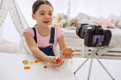 Cheerful girl showing handfuls of gummies to camera
