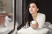 Beautiful woman on a white bed near the window with a cup of morning coffee