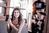 Delighted female vlogger holding her phone