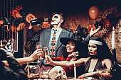 Young People Wearing Costumes Drinking Champagne