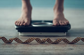 Close up. Young Woman Standing on Weigher on Floor