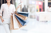 Happy brunette with shopping bags at mall. Sale.
