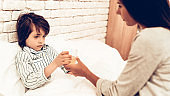 Mother Giving Medicine to Sick Son Lying Bed