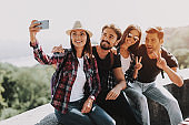 Young Smiling People Sitting in Park taking Selfie
