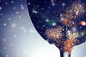 Colorful fireworks against the black silhouette of a wine glass with falling snow background.
