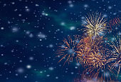 Colorful fireworks background with falling snow at night and with free space for text