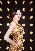 Superstar woman wearing golden shining dress posing