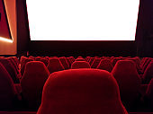 cinema - interior of a movie theatre with empty red and black seats with white screen - mock-up screen