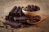 Raw cocoa beans, chocolate on wood background