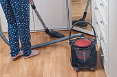 young woman vacuuming the house with the vacuum cleaner. housekeeping concept