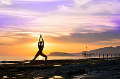 Silhouette Asia woman yoga on the beach at sunset
